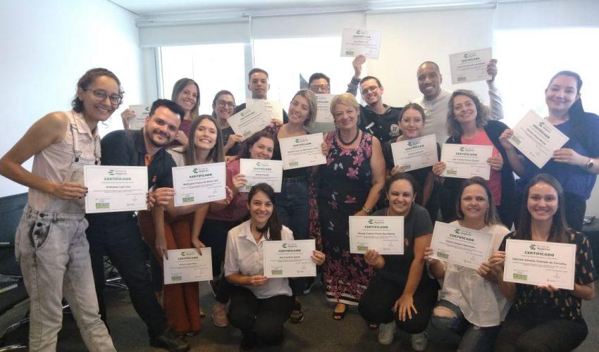Turma de formandos da Escola de Negócios da ACE, segurando os certificados de conclusão.