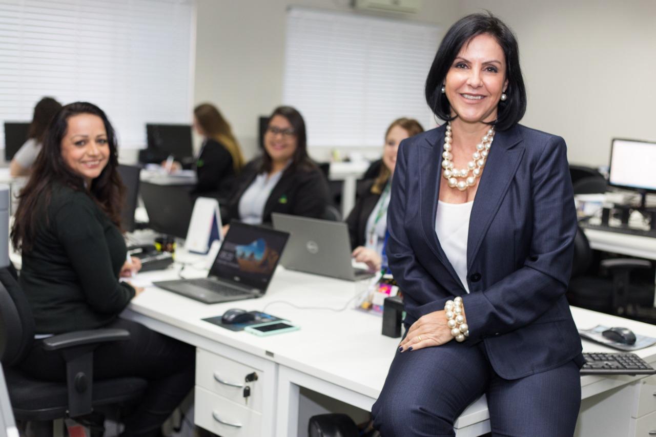 Leandra Diniz, vice-presidente da ACE e idealizadora da Escola, sentada em uma bancada com funcionárias da associação ao fundo, desfocadas.